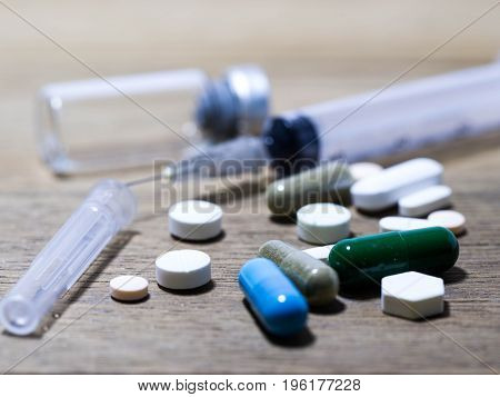 close up Drug and capsule and injection needle is on the wooden table Multicolored of drug and drug capsule.