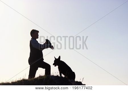 Man And His Dog Stand On Mountain Peak
