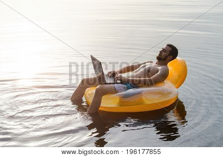 Man with laptop on a rubber ring in the water at sunset free space. Freelancer works.