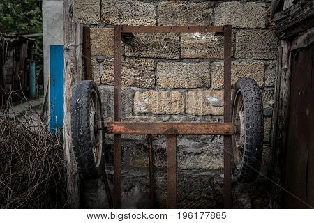 Old rusty cart with rubber wheels on a stone background
