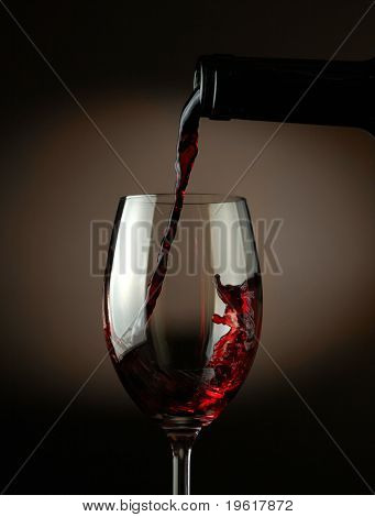 Red wine pouring into glass over dark background