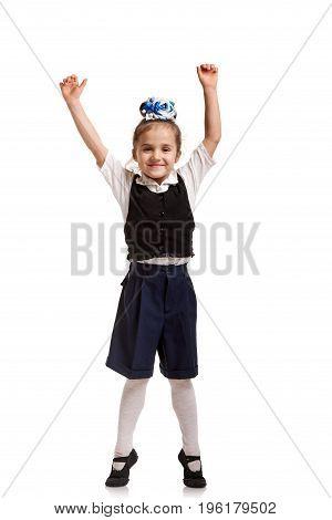 Positive little girl in school uniform jumping on white background