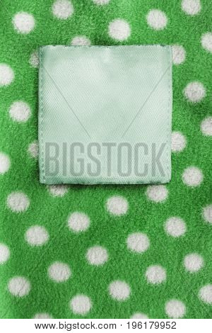 Blank clothes label on green polka dots fleece as a background