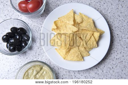 Plain nachos on a white plate with bowls of olives, tomatoes and guacamole
