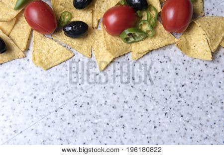 Background image of nachos, olives, tomatoes, and jalapeno peppers, with copy space