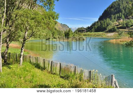 lake in alpine mountain surrounded by wooden fence
