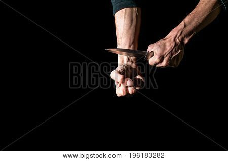 Man want to commit suicide by cutting his veins with knife. Low key image, isolated on black background.