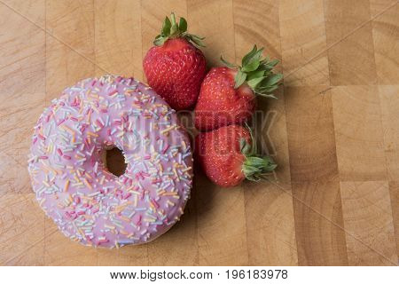 Strawberry donuts on a wooden background with strawberries