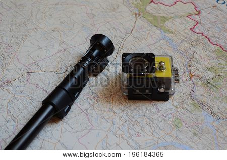 action camera with monopod lies on the geographical map
