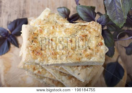 Cheese homemade bread with basil on a wooden board