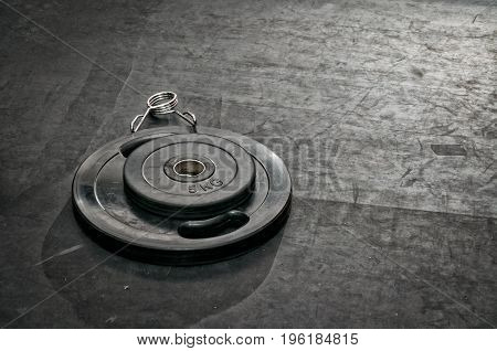 Bodybuilding gym equipment. Barbell weight plates on the gym floor.