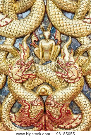 Golden dragon stucco with the small rabbit on the church wall in the Thai temple.(Public area not required Property Release)