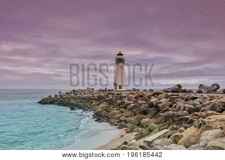 Dramatic Dusk over Santa Cruz Harbor Walton Lighthouse. Breakwater (Walton) Lighthouse, Santa Cruz, California, USA.