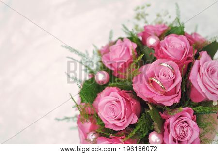 Wedding bouquet of pink roses lying on white floor