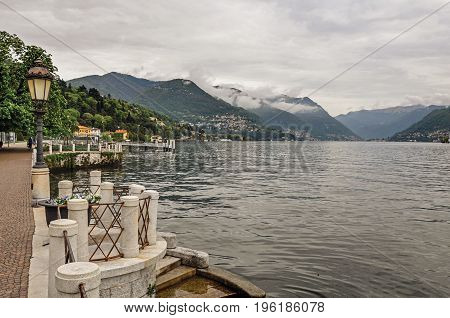 Walking view on Lake of Como and buildings in a cloudy rainy day. Near the city of Como, a pleasant town a few miles from Milan. Located in the Lombardy region, northern Italy