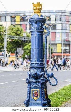 Old ancient blue pump of water with sculptures on it in Szczecin Poland.