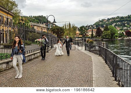 Como, Italy - May 06, 2013. View of newlyweds strolling along the promenade of Como Lake. Near the city of Como, a pleasant town a few miles from Milan. Located in the Lombardy region, northern Italy