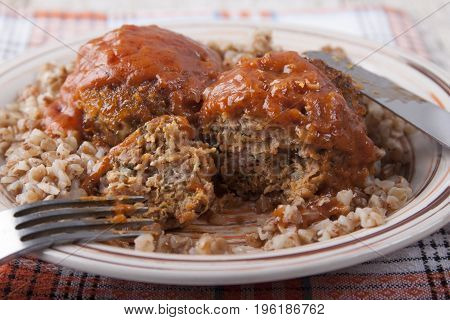 Meat-vegetable cutlets with tomato sauce and buckwheat porridge for garnish