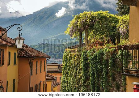 View of Como Lake, balconies with open blinds and bindweed in Bellagio, a charming tourist village between the lake and the mountains of the Alps. Located in the Lombardy region, northern Italy