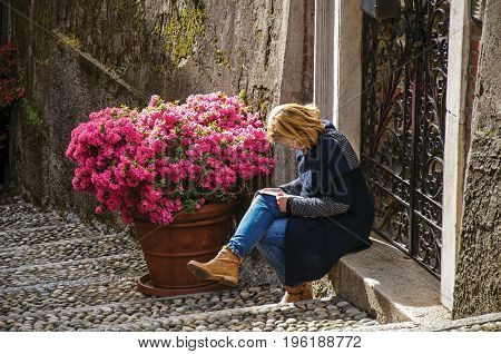 Como, Italy - May 06, 2013. View of alley in hillside with woman reading in front of a gate in Bellagio, a charming village between the lake and the mountains of Alps. Lombardy region, northern Italy