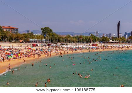 Barcelona, Spain - July 15, 2017: People rest on a sandy beach in the area Pablenou. Barcelona. Spain.