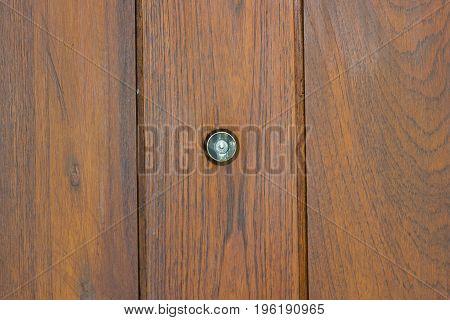 Peephole in the center of the wooden door.