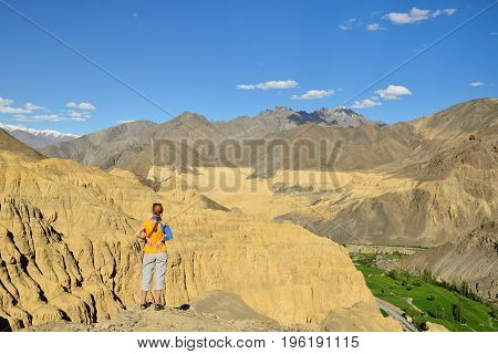 Tourist during expedition in the mountains Ladakh is admiring the beautiful Karakorum panorama in the vicinity of the Lamayuru town. Local are naming this rock formation with