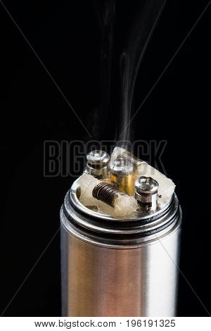 Electronic cigarette in working condition emits smoke on a black background