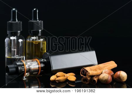 Black powerful electronic cigarette next to liquids with the taste of nuts and carica