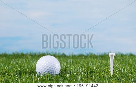 Golf ball on a green lawn against the sky