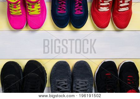 Sets of sports shoes on the wooden floor as a background for the inscription