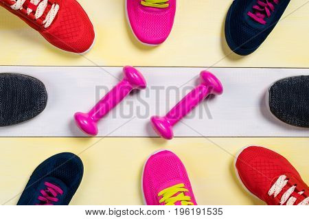 Scattered sports shoes on a multi-colored floor in the middle lies a set of sports dumbbells