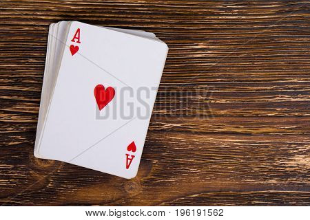 A deck of cards with an ace on a dark wooden table