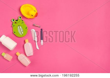 Baby accessories for bath with duck on pink background. Top view. Copy space. Still life. Flat lay