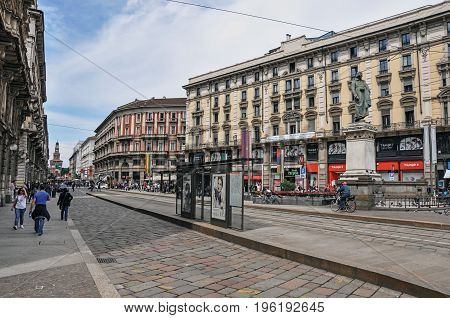 Milan, Italy - May 07, 2013. Street view with people, buildings and sculpture at the city center of Milan, a large and modern city. Located in the Lombardy region, northern Italy