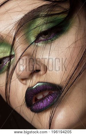 Beautiful girl with spring green makeup and vampire lips. beauty face. Photos shot in studio