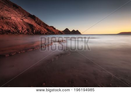 Moody sunset at Three Cliffs Bay on the Gower peninsula, Swansea, South Wales, UK