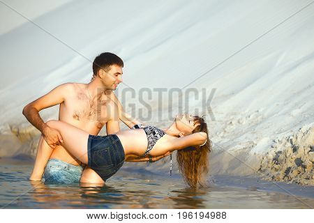 Beach lovers on romantic travel honeymoon vacation summer holidays romance. Young happy girl and handsome man plaing and embracing on water