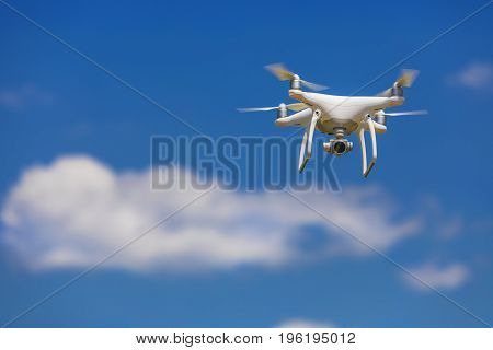 Professional camera drone flying in clear blue sky partly clouded.