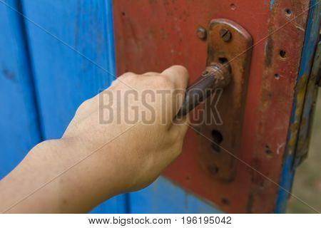 Young woman's hand open old wooden door.