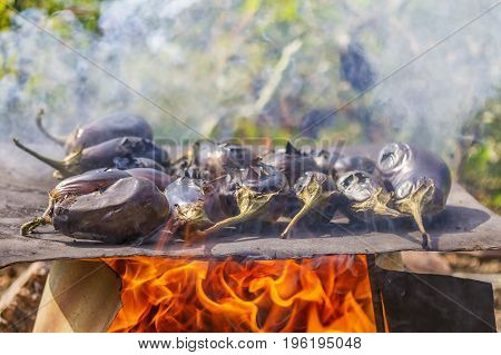 Eggplants cooking on a metal plate over open fire. Eggplants baking on the roast natural outdoor food.