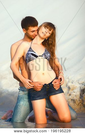 romantic couple on travel honeymoon vacation summer holidays romance. Young happy girl and man kissing and embracing on water