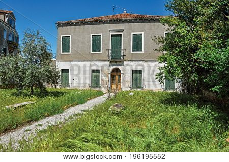 Front view of house with wheat in the front yard in Murano, a small and pleasant town on top of islands near Venice. Located in the Veneto region, northern Italy