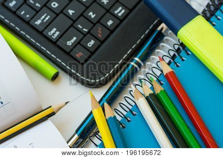 Top view school supplies laptop tablet keyboard multicolored pencils highlighter pen opened mathematics workbook with formula white desktop learning studying college