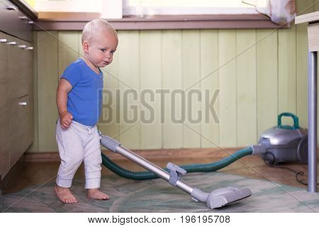 Funny toddler cleaning up the kitchen with hoover.
