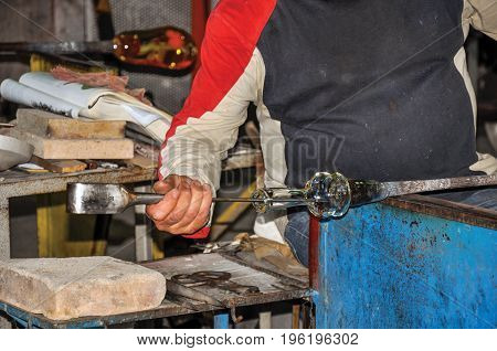 Detail of craftsman hands working on glass sculpture in a Murano workshop, a small and pleasant town on top of islands near Venice. Located in the Veneto region, northern Italy