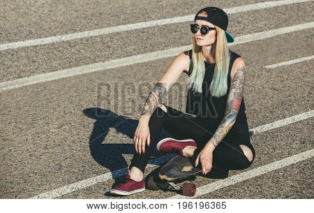A Beautiful, Sexy Hipster Blonde With Blue Hair In Tattoo Sits On A Longboard  With Glasses And A Ca