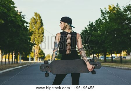 A Beautiful, Sexy Hipster Blonde With Blue Hair In Tattoo Stands With A Longboard It Is Turned Back