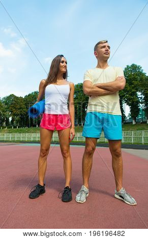 sport and fitness couple. man and woman redy for the training standing at stadium at sunn day with exersize mat. sexy girl and handsome man