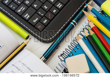 Top view school supplies laptop tablet keyboard multicolored pencils highlighter rubber pen opened mathematics workbook with formula white desktop learning studying college